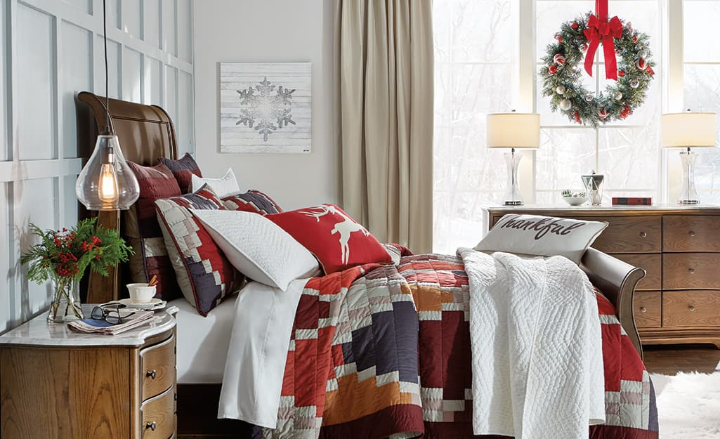 A bedroom with red holiday decorations and a wreath hanging from the window.