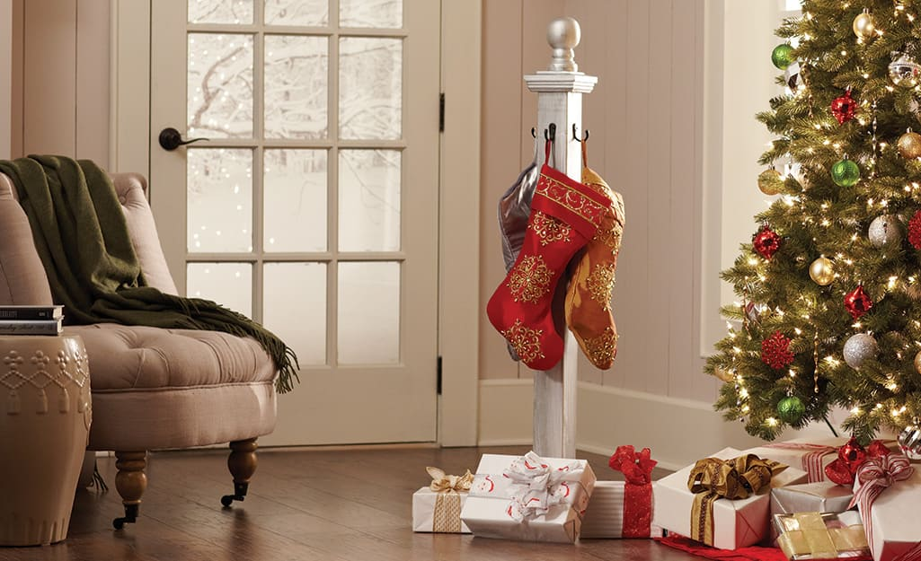 Stockings hang from hooks on a wooden pole over a pile of wrapped presents next to a decorated Christmas tree.
