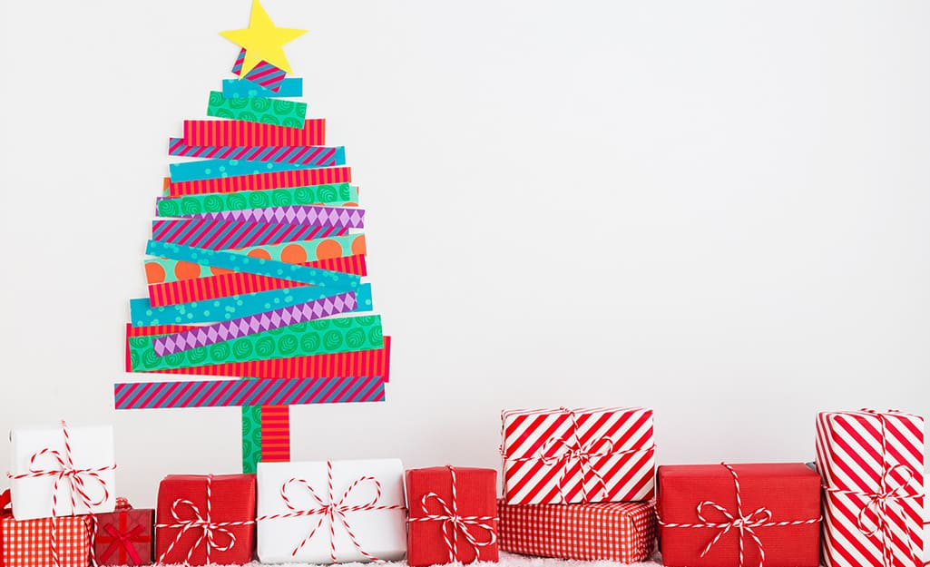 Presents sit beneath a depiction of a Christmas tree on the wall made from different patterns of washi tape.