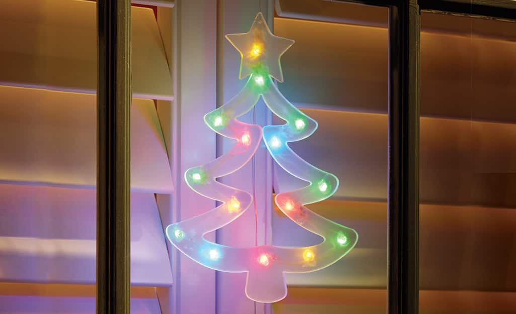 A multicolor lighted Christmas tree window cling attached to the outside of a window pane.