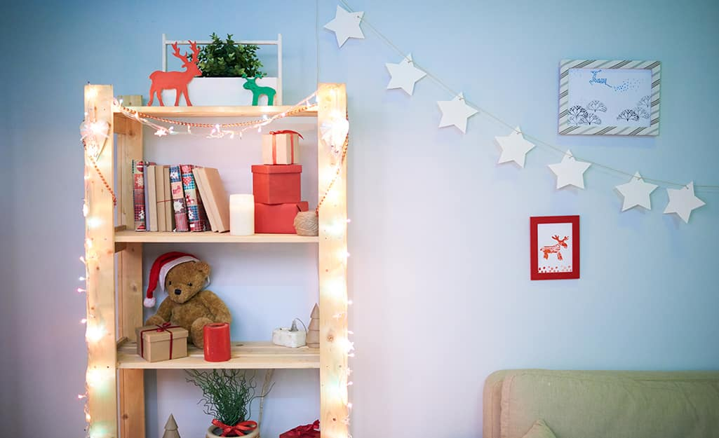A bookshelf decorated with small holiday decorations and mini string lights.