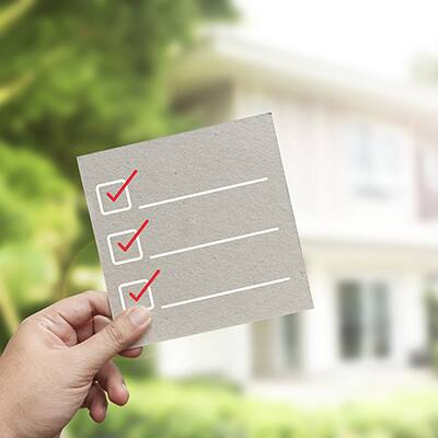 A hand holding up a blank checklist in front of a home.