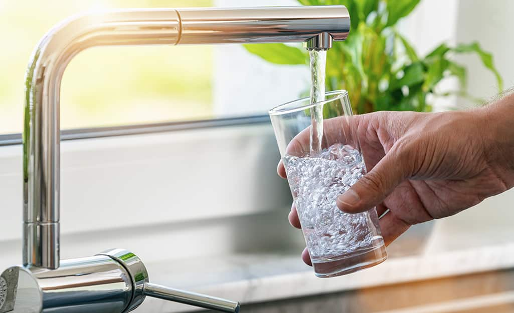 A person fills a glass of water from a tap.