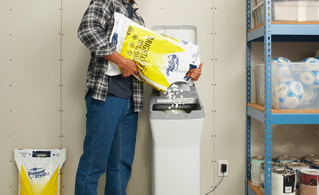 A person adds water softener salt to a water softener tank.