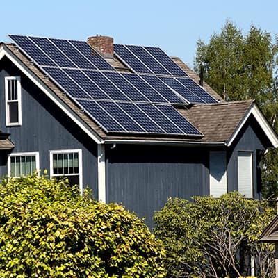 Sun shining on solar panels installed on a roof.