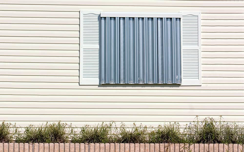 A metal barricade covers a window for storm protection.