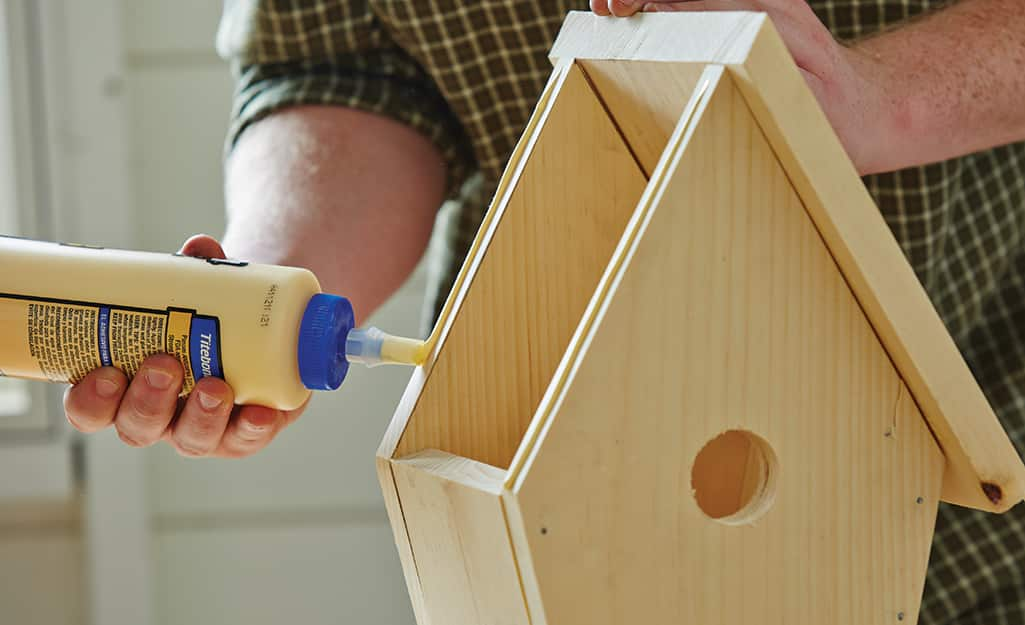 A person glues the top of a birdhouse onto the main part of the house