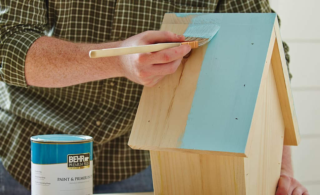 A person paints the roof of a birdhouse a light blue