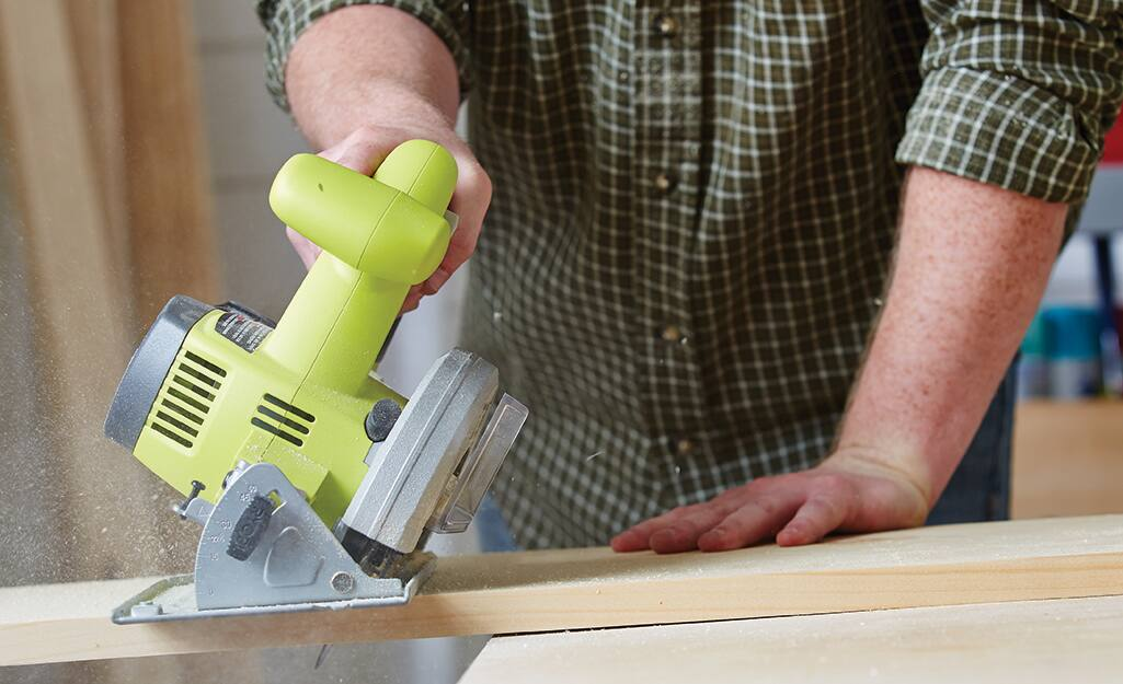 A person cuts a board with a circular saw while building a birdhouse.