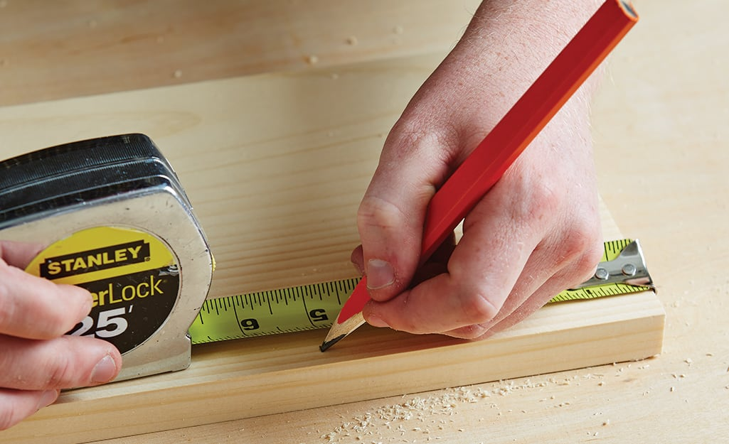 A person uses a pencil to mark a measurement on a board made with a tape measure