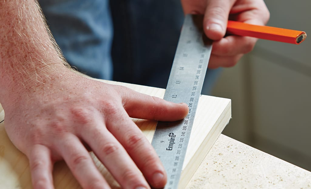 A person uses a pencil and a ruler to mark a cut line on a piece of wood needed to build a birdhouse