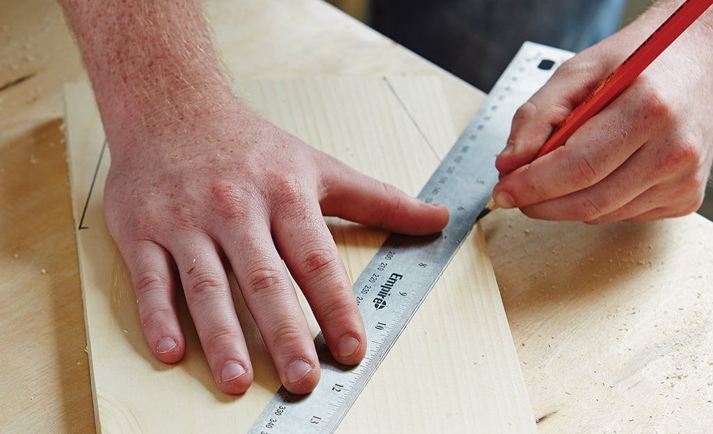 A person uses a pencil and a ruler to mark the bottom cut lines for a DIY birdhouse