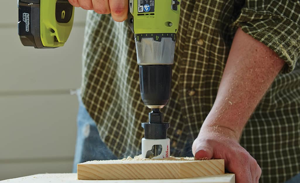 A person uses a drill fitted with a hole saw to make the entrance to a birdhouse
