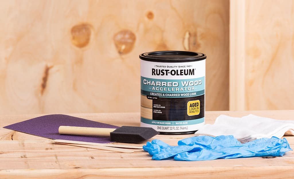 A can of wood stain and wood staining supplies sit on a piece of wood.