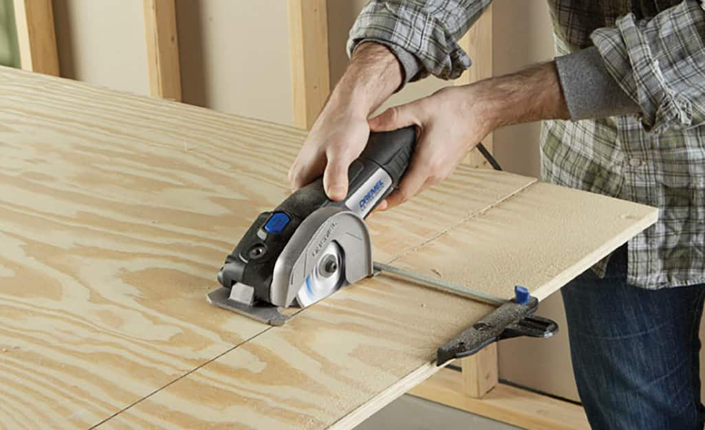 A man uses a handheld circular saw to cut a board.