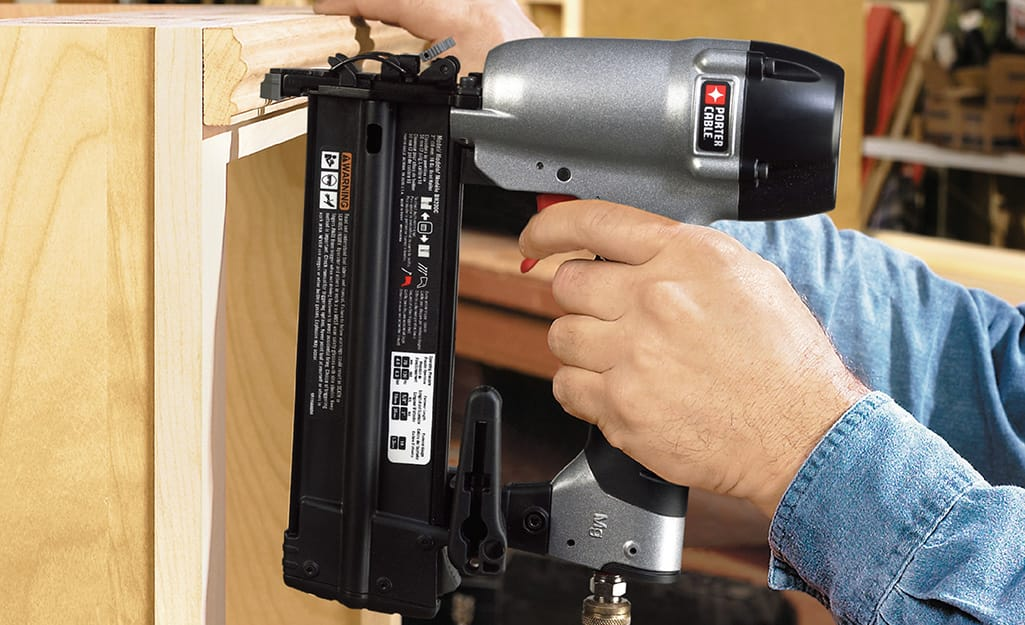 Someone using a finish nailer to fasten moulding along the top of a bookshelf.