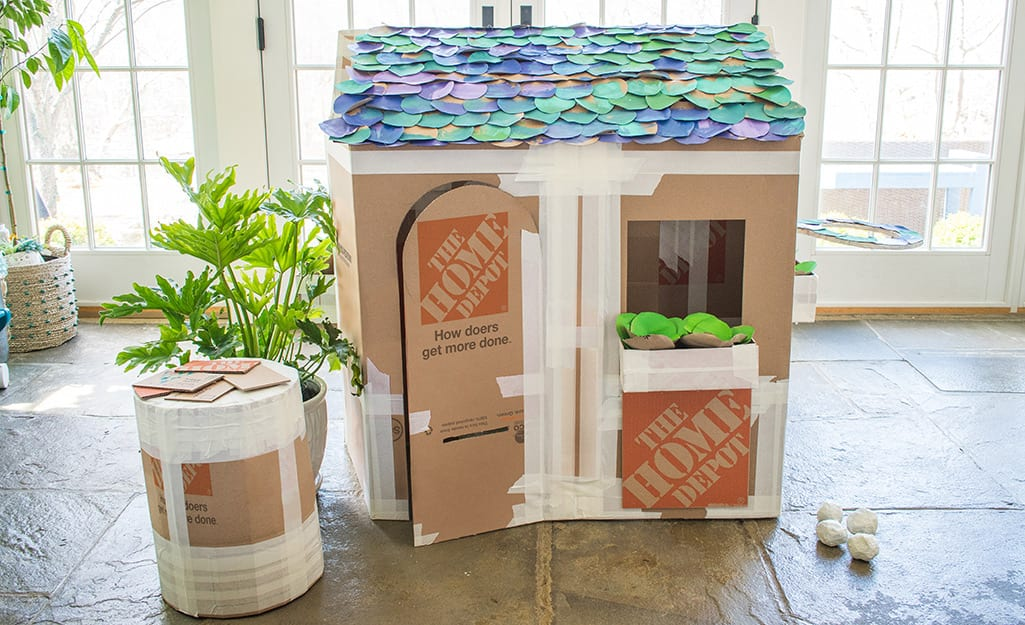 A deluxe cardboard playhouse with colorful paper shingles.