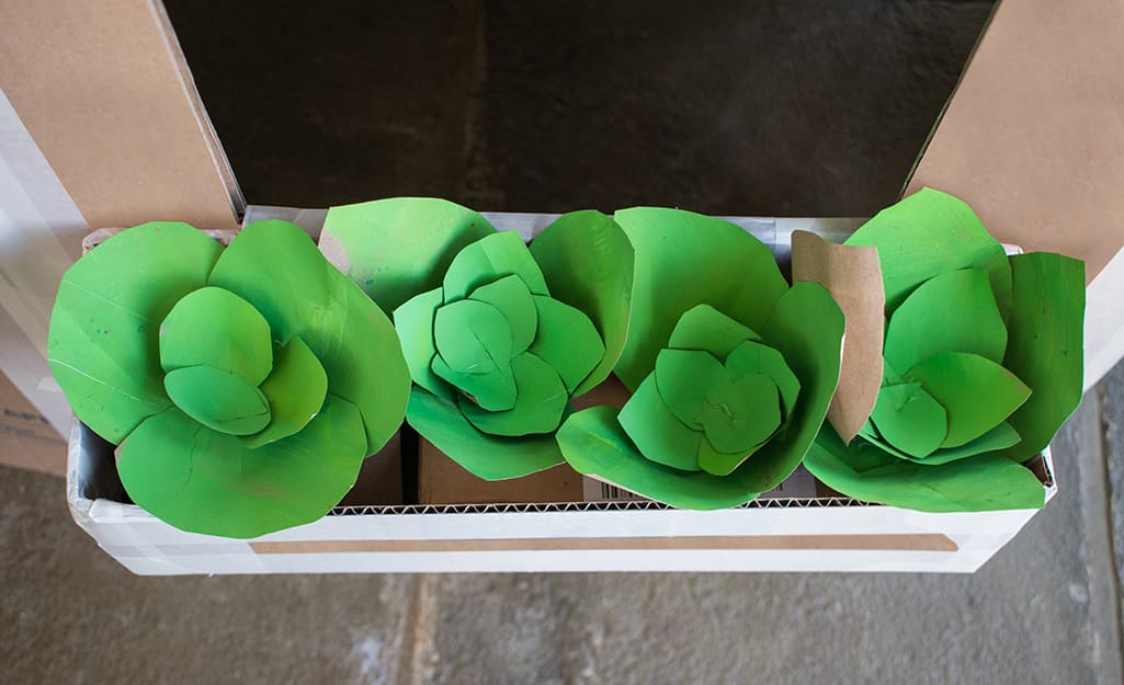 A box of paper flowers with green petals.