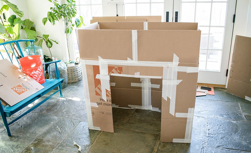 A partially assembled deluxe cardboard playhouse.
