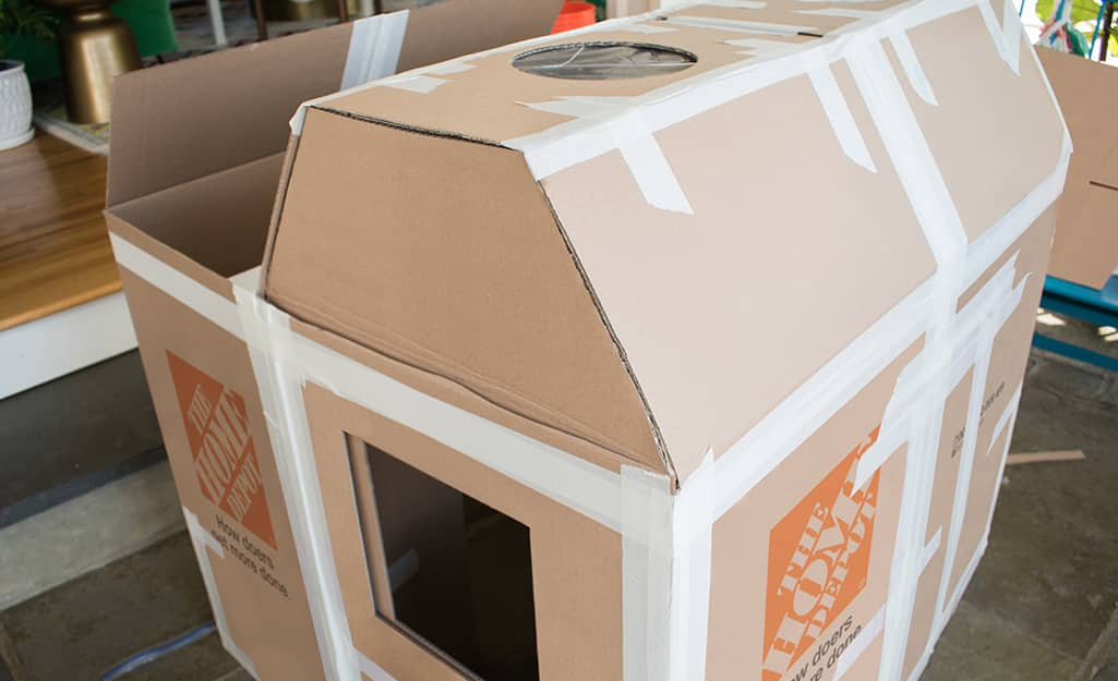 Skylights attached to the roof of a deluxe cardboard playhouse.