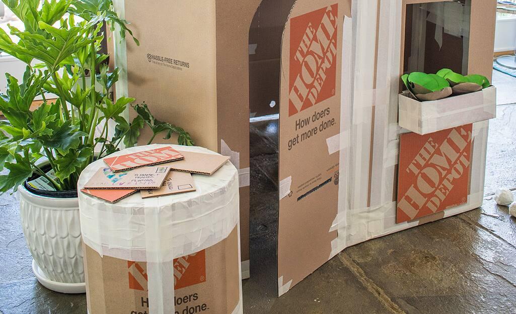 A cardboard play ottoman next to a cardboard playhouse.