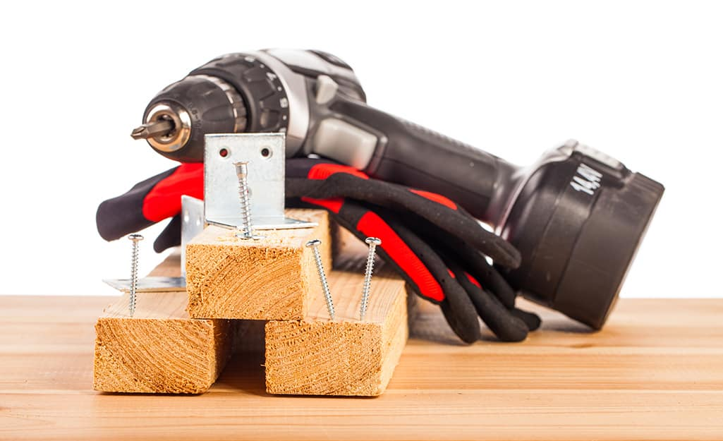 A cordless drill resting on top of wood boards.