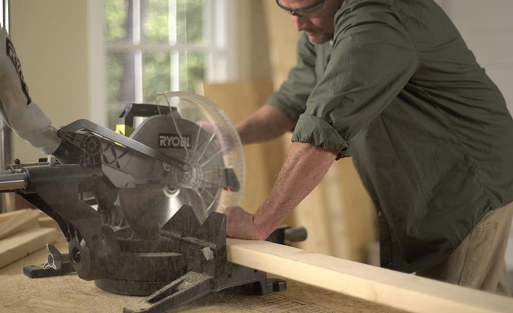 A man using a circular saw to cut a piece of lumber.