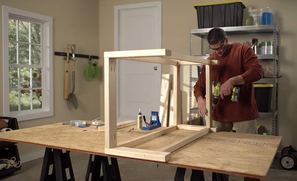 A man using a drill to assemble a DIY coffee table.