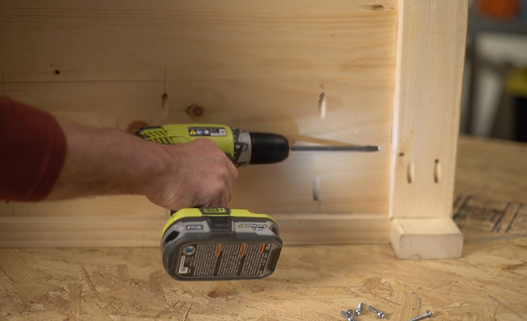 A man using a drill to make pocket holes in a DIY coffee table.