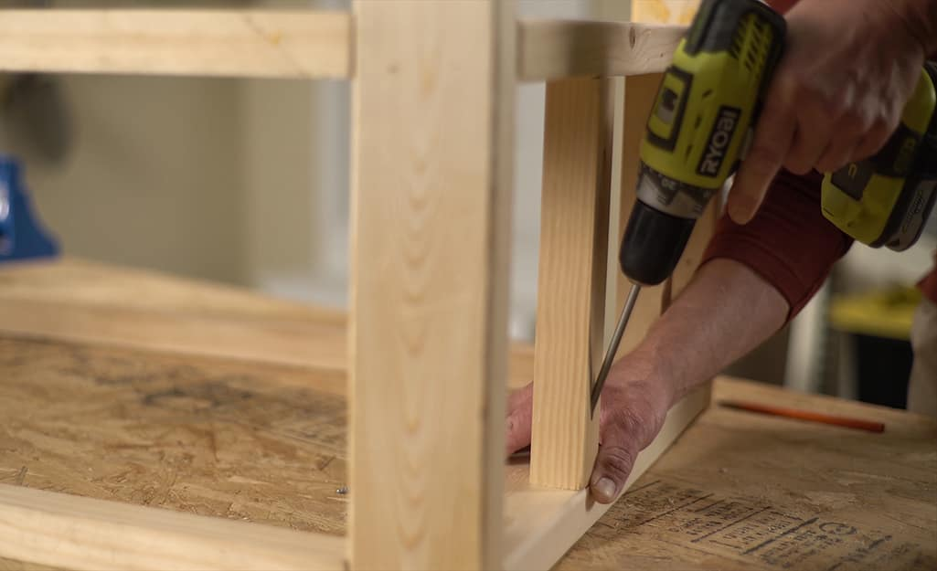 A  man using a drill to make pocket holes in the legs of a DIY coffee table.
