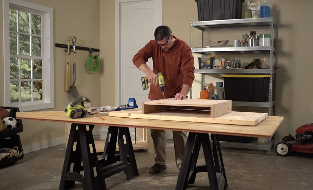 A man using a drill to screw together a shelf for a DIY coffee table.