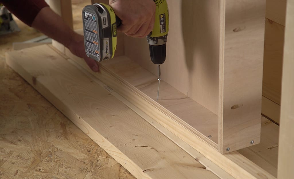 Someone using a drill to screw  a shelf to the back of a DIY coffee table.