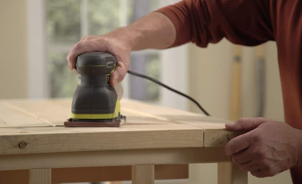 A man using a power sander to sand the top of a DIY coffee table.