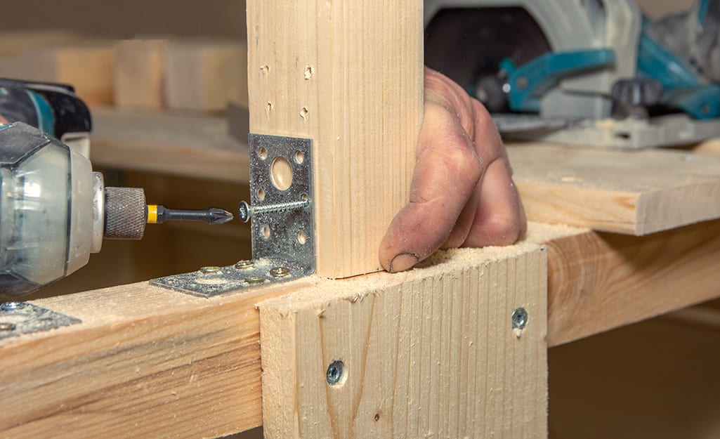 Man attaches a deck board to an inner joist with a power drill.