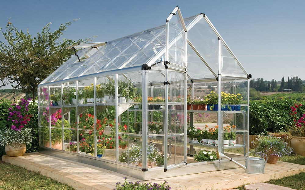 Greenhouse kit with a clear roof and panels, sitting on a foundation, with plants inside.