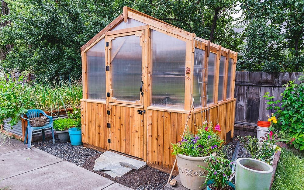 Greenhouse built with wood on a bed of gravel.