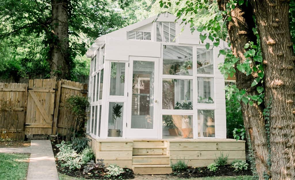 A white greenhouse made of windows in a yard