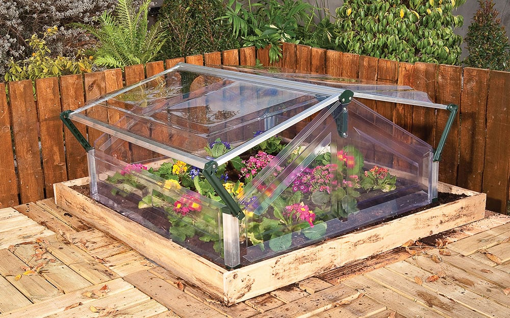 Mini DIY greenhouse with plants and a wooden base.