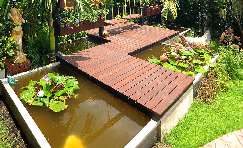 An above ground fish pond built under a wood walkway.