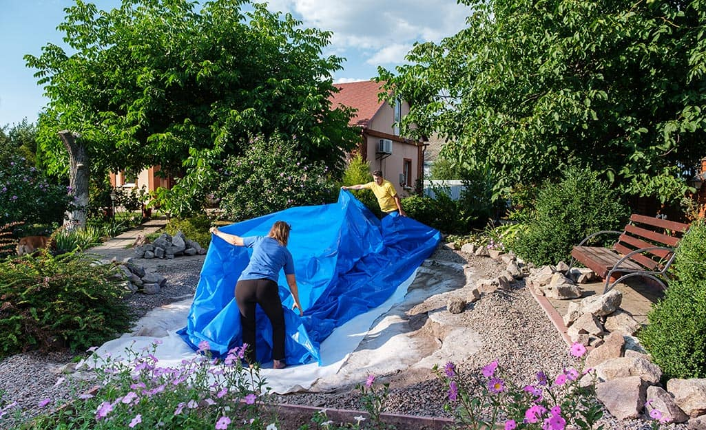 Two people laying a pond liner as they build an in-ground fish pond.