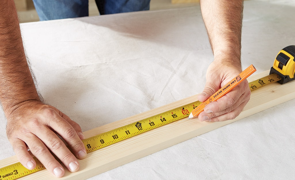 A man uses a pencil and measuring tape to measure and mark wood.