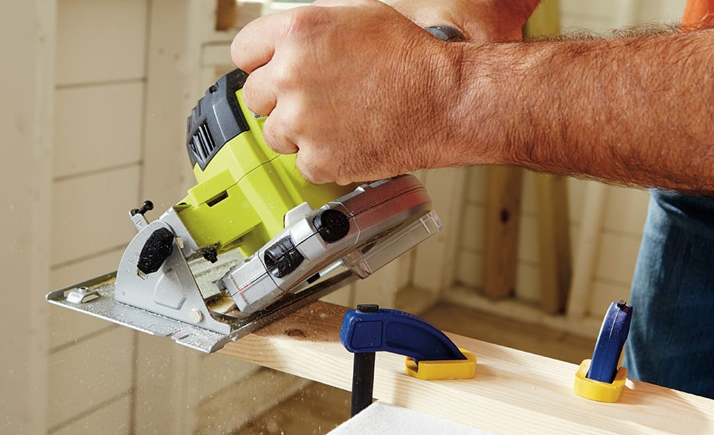 A person uses a circular saw to cut wood.