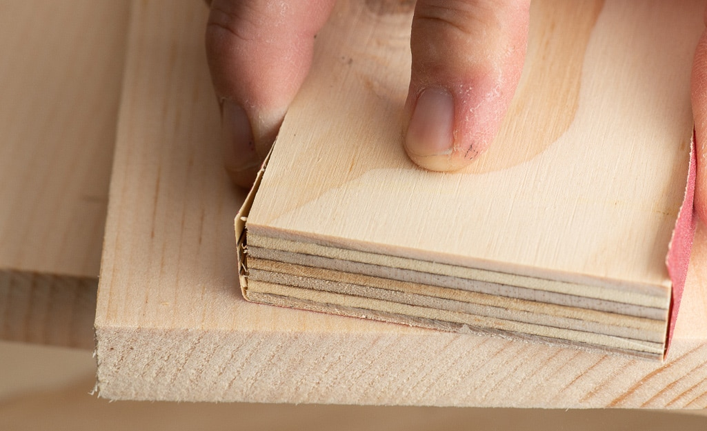 A person examining the quality of lumber.