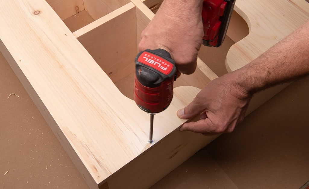 A person drilling screws into the backing of the cubby storage.