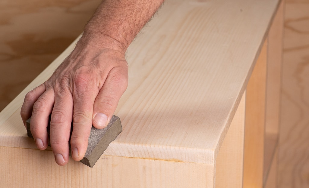 A person sanding the edges of the cubby.