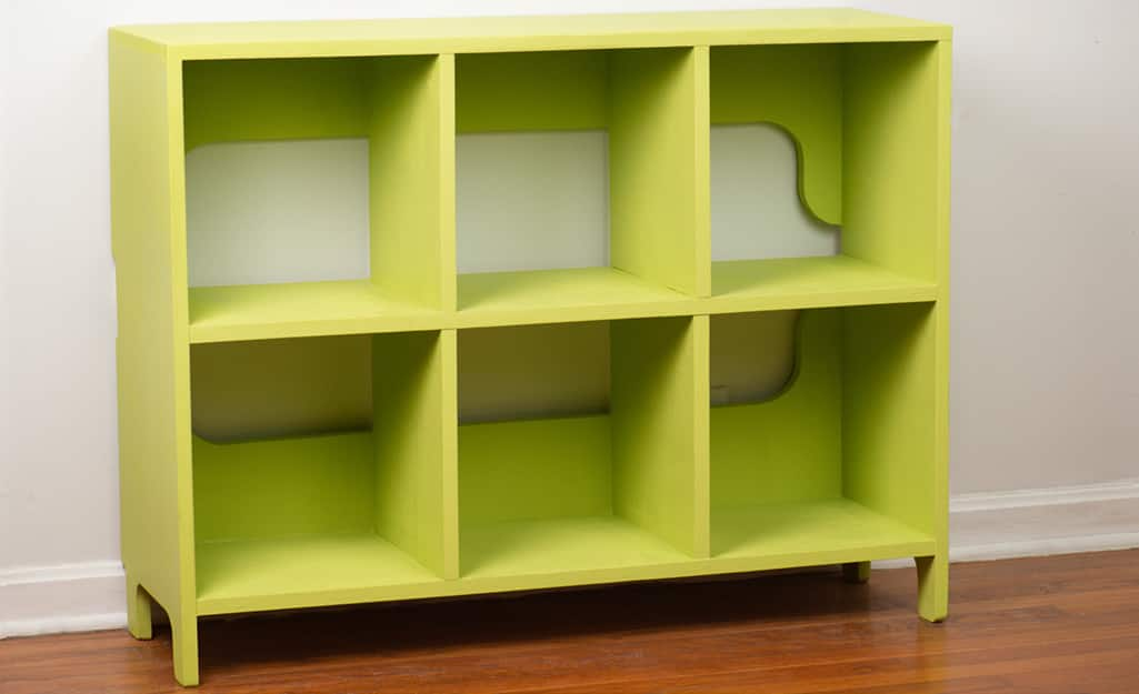A finished kids cubby storage unit painted green.
