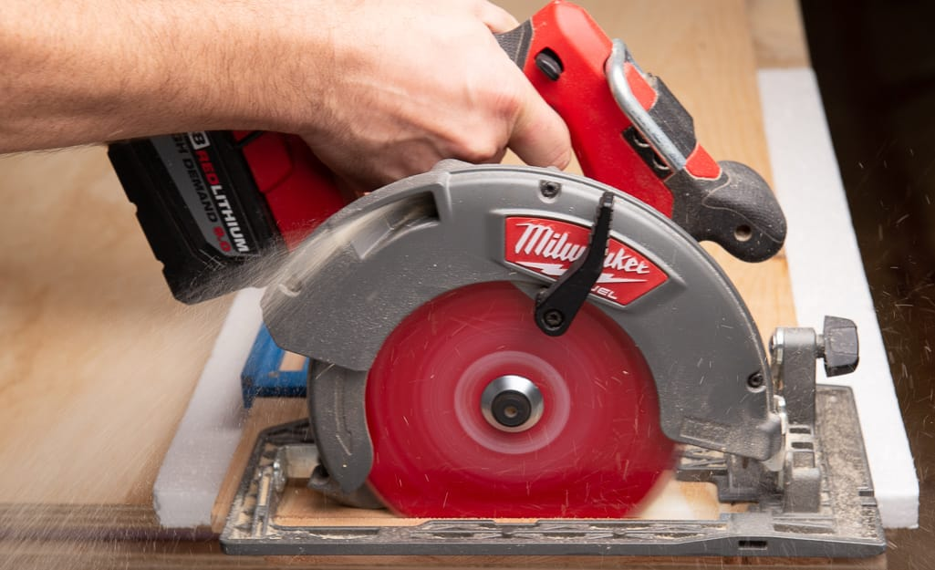 A person cutting wood with a circular saw.