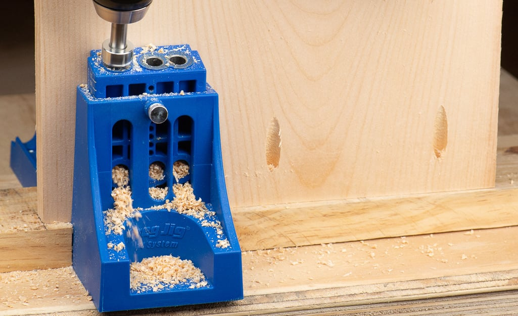 A person using a pocket hole guide to drill into wood.