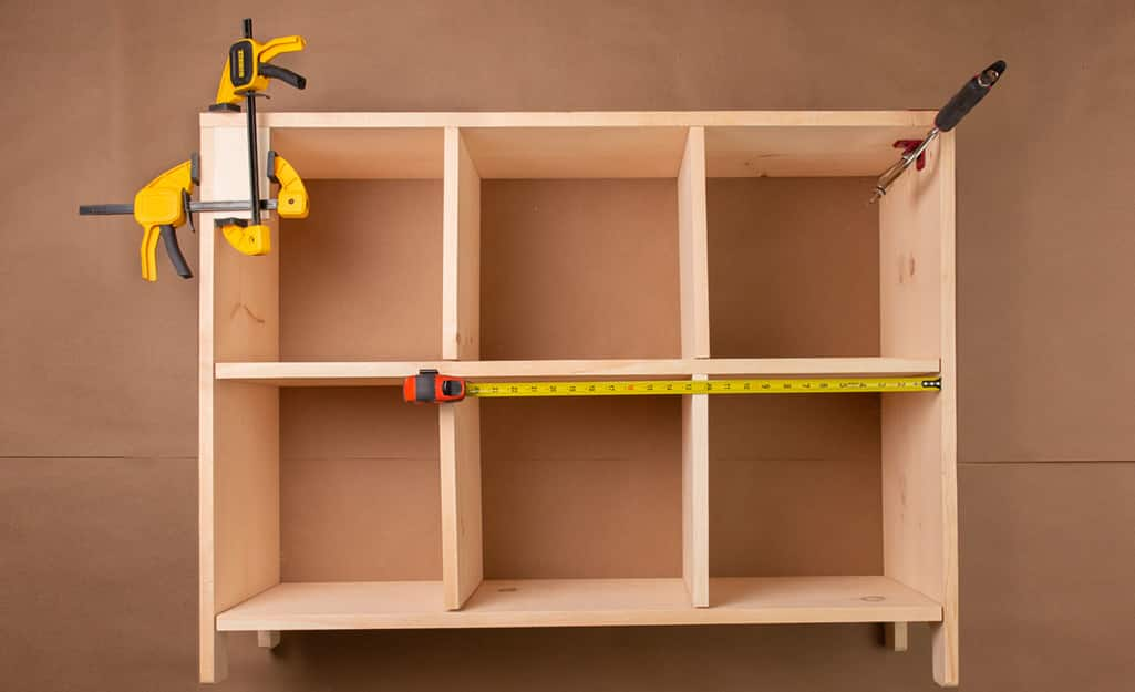 A cubby storage clamped together to dry fit the boards.