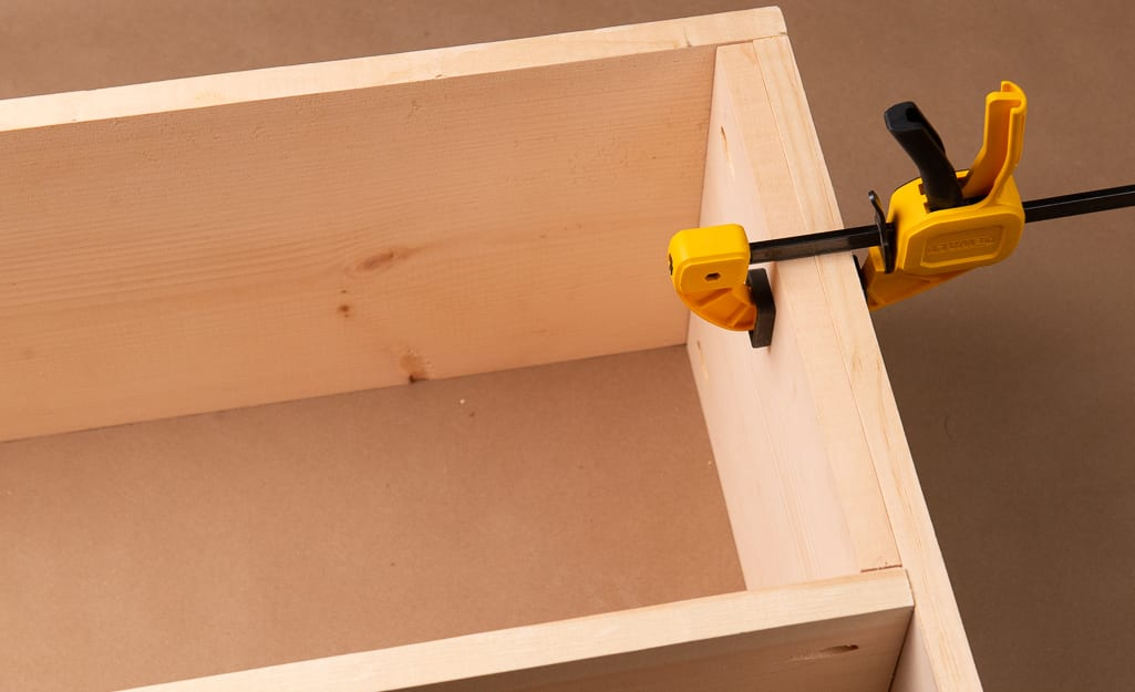 A clamp holding glued boards in place on a cubby.